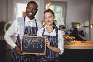 Smiling waiter and waitress showing chalkboard with open sign