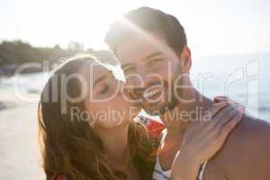 Portrait of smiling man being kissed by his girlfriend at beach