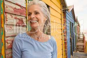 Close up of smiling senior woman standing by wall