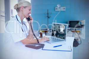 Composite image of smiling doctor using laptop while talking on telephone