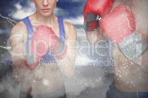 Composite image of portrait of man and woman wearing boxing gloves