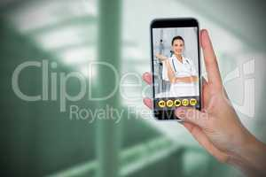 Composite image of human hand holding mobile phone against white background