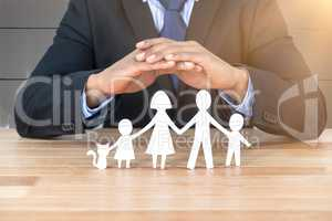 Composite image of underwriter protecting family in paper with his hands