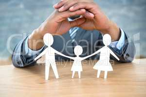 Composite image of hand protecting a family in paper