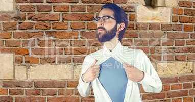 Hipster tearing shirt against brick wall