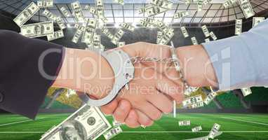Business people with handcuffs shaking hands at football stadium representing corruption