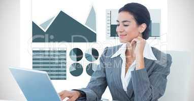 Confident businesswoman using laptop against graph background