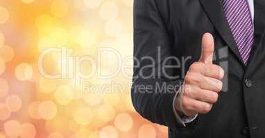 Midsection of businessman gesturing thumb up over bokeh