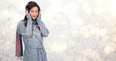Woman in winter coat listening to music on headphones