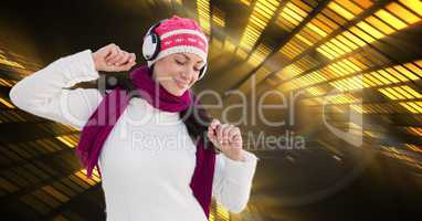Woman in warm clothing listening to music through headphones