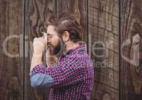 Side view of male hipster photographing against wooden wall