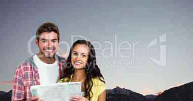 Portrait of happy couple holding map against clear sky