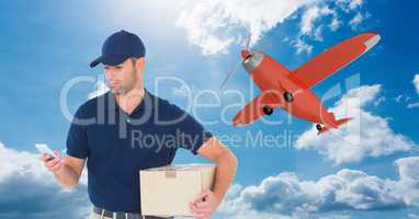 Delivery man using mobile phone while holding parcel against airplane flying in sky