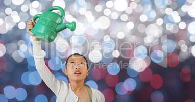 Little girl holding watering can over blur background