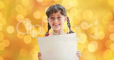 Happy girl holding placard over defocused background