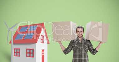 Portrait of delivery man carrying cardboard boxes by house and windmill