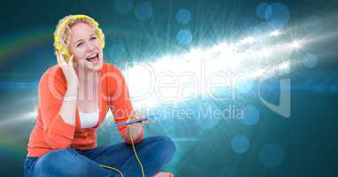 Young woman singing and listening to songs on headphones