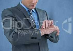 Midsection of businessman touching wrist over blue background