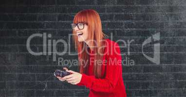 Redhead hipster playing video game against wall