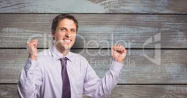 Portrait of successful businessman clenching teeth and fists against wooden wall