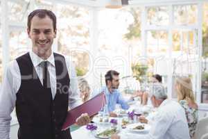 Smiling waiter holding menu while friends dining in background