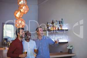 Three friends cheering and drinking beer while watching match