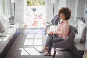 Portrait of beautiful woman sitting on arm chair