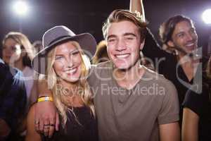 Portrait of smiling friends standing at nightclub