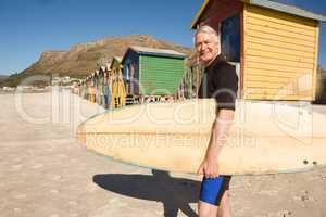 Portrait of smiling man carrying surfboard standing against beach hut