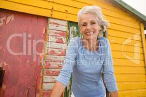 Low angle view of happy woman looking away against wall