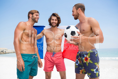 Portrait of man holding French flag while standing with male friends at beach