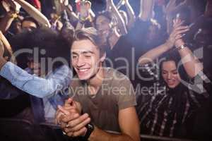 Young man amidst crowd enjoying at nightclub
