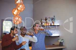 Three friends drinking beer while watching match