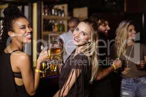 Portrait of female friends having drink at counter