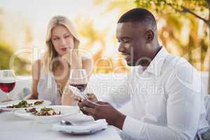 Man ignoring bored woman while using mobile phone