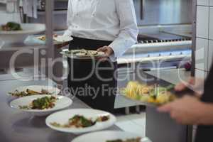 Chefs holding his food plates in the commercial kitchen