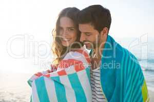 Happy young couple wrapped in blanket at beach