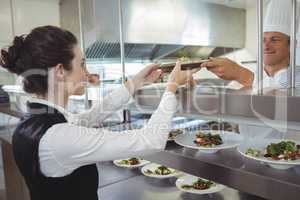 Chef handing food dish to waitress at order station