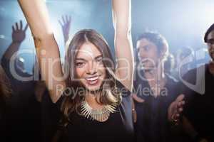 Portrait of happy woman dancing at nightclub