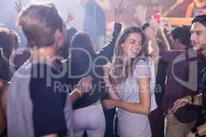 Happy people dancing at nightclub