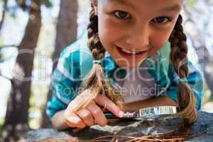 Smiling girl using magnifying glass in the forest