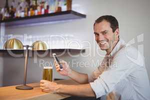Man using mobile phone while having beer