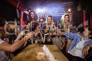 Cheerful friends toasting drink at table with performer singing on stage