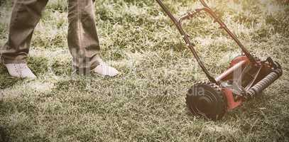 Man with lawnmower on grass