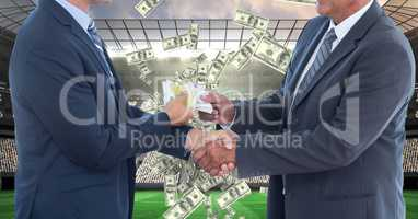 Midsection of businessmen exchanging money while shaking hands on soccer field representing corrupti