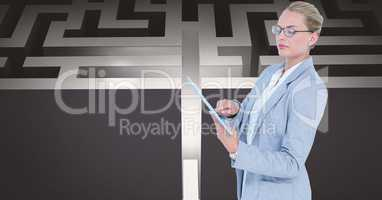 Confident businesswoman using tablet PC against maze