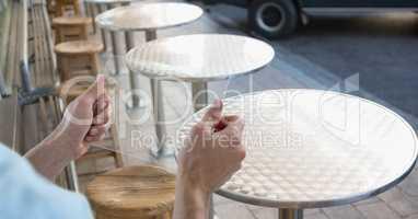 Hands holding transparent device at sidewalk cafe