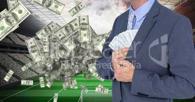 Midsection of businessman hiding money at football stadium representing corruption