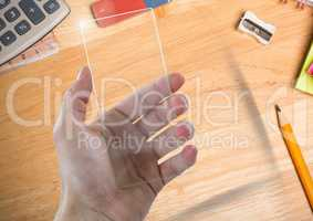 Hand with glass screen on table with objects