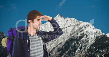 Male traveler shielding eyes while carrying backpack on mountain